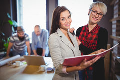 Happy female coworkers standing with file in creative office Royalty Free Stock Photos
