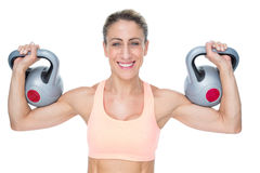 Happy female crossfitter lifting kettlebells looking at camera Stock Photos