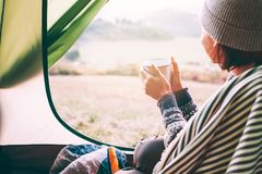 Happy female with cup of hot tea sits in camping tent, looks out and enjoys a new day beginning royalty free stock image