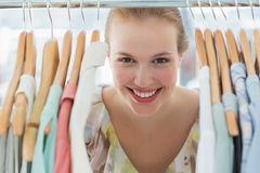 Happy female customer amid clothes rack Stock Photos