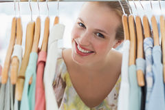 Happy female customer amid clothes rack Stock Photography