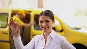 Smiling businesswoman show ok. Blurred delivery van and courier at the background. Happy Female Customer In Business Suit Shows Ok Sing For The Delivery Service stock video