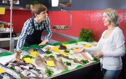 Happy female customer choosing and buying fish Stock Photo