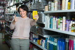 Happy female customer choosing conditioner for hair in beauty st Stock Images