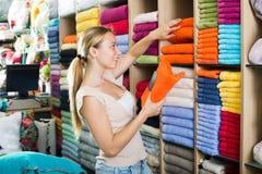 Happy female customer choosing towels Royalty Free Stock Photos