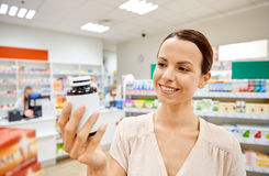 Happy female customer with drug jar at pharmacy Stock Photos