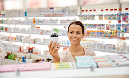 Happy female customer with drug jar at pharmacy Stock Photography