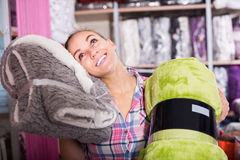 Happy female customer looking through coverlets Stock Image