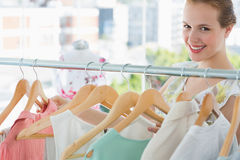 Happy female customer selecting clothes in store Stock Images