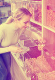 Happy female customer selecting various nuts. In the store with ecological goods Stock Image