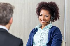 Happy Female Customer Service Agent Looking At. Happy female customer service agent wearing headset looking at manager in office Royalty Free Stock Image