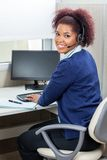 Happy Female Customer Service Executive Using. Side view portrait of happy female customer service executive using computer at desk in office Royalty Free Stock Images