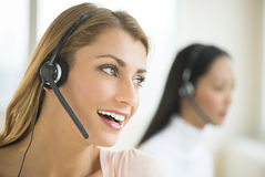 Happy Female Customer Service Representative Looking Away. Close-up of happy female customer service representative looking away with colleague in background Stock Image