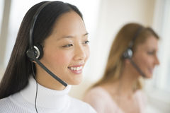 Happy Female Customer Service Representative Looking Away. Happy female customer service representative wearing headset looking away with colleague in background Royalty Free Stock Images