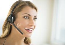 Happy Female Customer Service Representative Looking Away. Happy young female customer service representative wearing headset looking away Royalty Free Stock Images
