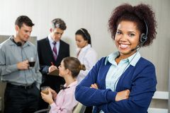 Happy Female Customer Service Representative. Portrait of happy female customer service representative standing arms crossed while team discussing in background Royalty Free Stock Image