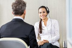 Happy Female Customer Service Representative. Wearing headphones talking to manager in office Stock Photography