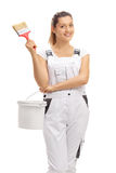Happy female decorator holding a paintbrush and a color bucket Stock Photos