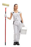 Happy female decorator with paint roller and paint bucket Royalty Free Stock Photos