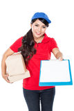 Happy Female delivery service with clipboard. A portrait of Happy Female delivery service with clipboard and package. stretched her arm out require signature Royalty Free Stock Images