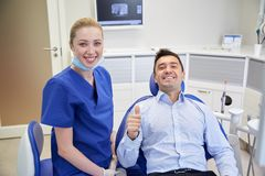 Happy female dentist with man patient at clinic Royalty Free Stock Image