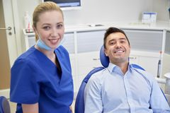 Happy female dentist with man patient at clinic Stock Images
