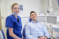 Happy female dentist with man patient at clinic Stock Image