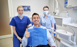 Happy female dentists with man patient at clinic Royalty Free Stock Images