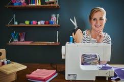 Happy female designer sitting at desk stock photos