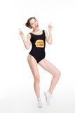 Happy female in designer swimwear pointing up with both hands Royalty Free Stock Photos