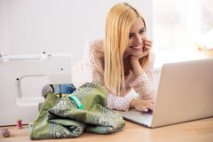 Happy female designer using laptop. In workshop Stock Photos