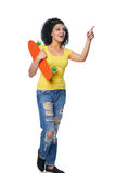 Happy female in distressed jeans with skateboard pointing to side. Full length surprised mixed race african american - caucasian female in distressed jeans with stock photography