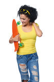 Happy female in distressed jeans with skateboard Royalty Free Stock Images