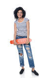 Happy female in distressed jeans with skateboard Stock Photography