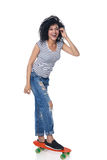 Happy female in distressed jeans with skateboard Royalty Free Stock Photo