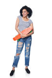 Happy female in distressed jeans with skateboard. Happy smiling mixed race african american - caucasian female in distressed jeans with skateboard looking away royalty free stock photos