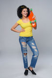 Happy female in distressed jeans with skateboard Royalty Free Stock Image