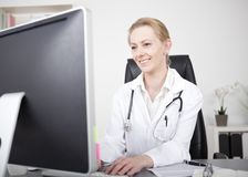 Happy Female Doctor Busy Chatting at her Computer. Happy Adult Female Doctor Sitting at her Table with Stethoscope on her Shoulders Busy Chatting Using her Royalty Free Stock Images