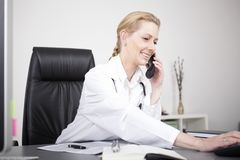Happy Female Doctor Calling Through Telephone Stock Image