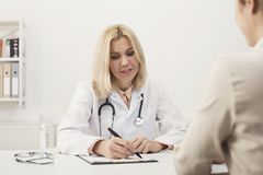 Happy doctor consulting woman in hospital royalty free stock photography