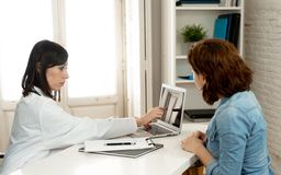Professional woman Doctor having consultation showing test results on laptop to inform patient. Happy female doctor explaining treatment and diagnosis showing stock photos