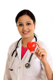 Happy female doctor holding a beautiful red heart shape Stock Photo