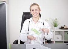 Happy Female Doctor Holding a Fan of 100 Bills Stock Images