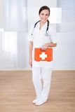 Happy female doctor holding first aid box. Portrait of happy young female doctor holding first aid box in hospital Stock Photo