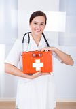 Happy Female Doctor Holding First Aid Box. Portrait of happy young female doctor holding first aid box in hospital Stock Image