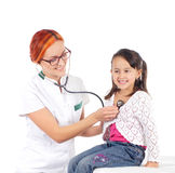 A happy female doctor inspecting a little brunette girl Royalty Free Stock Image