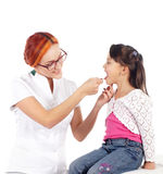 A happy female doctor inspecting a little brunette girl Royalty Free Stock Photo