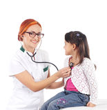 A happy female doctor inspecting a little brunette girl Royalty Free Stock Images