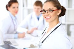 Happy female doctor keeping medical clipboard while medical staff are at the background Stock Photography
