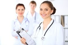 Happy female doctor keeping medical clipboard while medical staff are at the background Stock Images